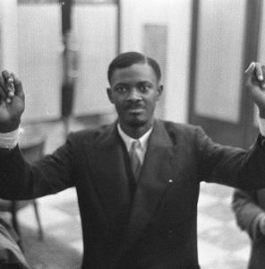 Fotografia de Patrice Lumumba, em Bruxelas, erguendo os braços em sinal de vitória e liberdade – Autor: Harry Pot [CC0], via Wikimedia Commons
