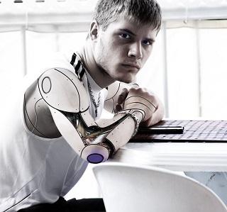 homem com braço artificial sentado de frente para mesa